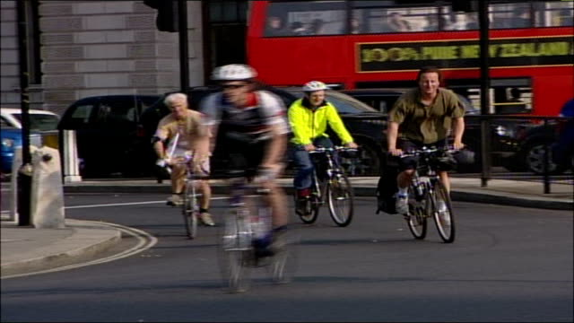 Politicians fly St George flag ENGLAND London EXT David Cameron MP wearing black shorts and baggy green tshirt as cycling towards with St George flag...