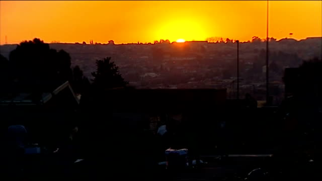 england beat platinum stars in warm-up match; south africa: soweto: ext / dusk pedestrians along main road with sunset behind sun setting over soweto... - ソウェト点の映像素材/bロール