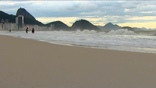 unease amongst brazilians about cost of staging tournament brazil rio de janiero ext waves crashing on beach high angle view rio cityscape sugar loaf... - 2014年点の映像素材/bロール