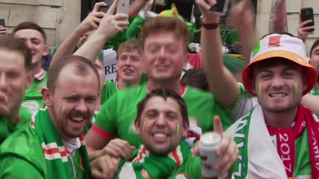 wales v republic of ireland buildup wales cardiff ext wales flag hanging from city centre lampost tilt down to republic of ireland football fans... - championships stock videos & royalty-free footage