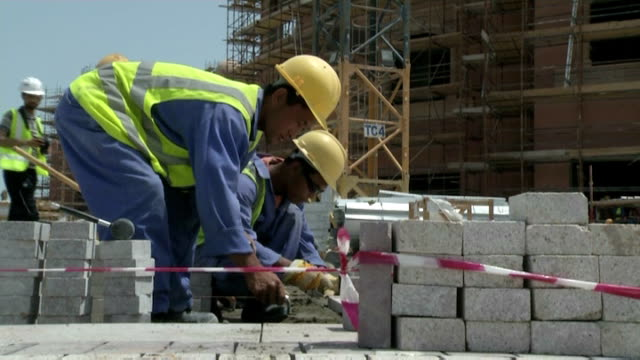 Construction sites with building inspectors EXT Men working laying stones or bricks for paved area and using rubber hammer to put into place /...