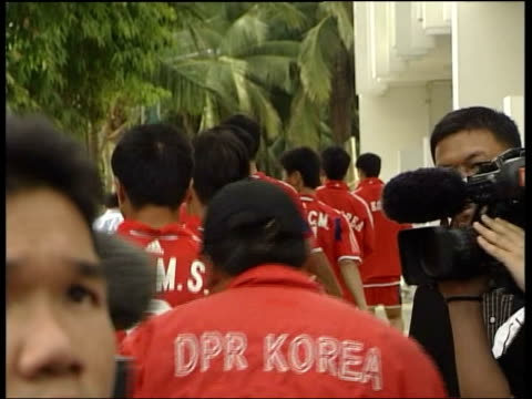 World Cup qualifying matches THAILAND Bangkok Japanese photographer Media surround coach as North Korean football players emerge for training session...