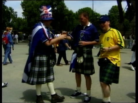 scottish fans in paris; france: paris: ext scotland fans talking about experiences so far scotland fans in football shirts and kilts holding beers... - kilt stock videos & royalty-free footage