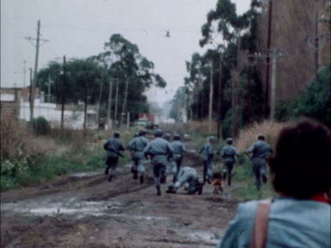 armoured car and troops out group run with dog one falls men one crawls on ground woman bungalow to car soldier with rifle by tree building troops... - 1978 stock videos & royalty-free footage