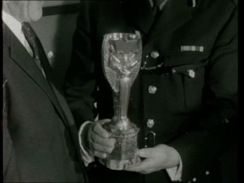 world cup trophy recovered by pickles the dog; england: london: cannon row police station: int cup held: pill out police officer and officials cup... - イングランド点の映像素材/bロール