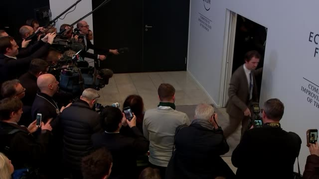 Angela Merkel speech / Brexit deadlock SWITZERLAND Davos INT High angle view of Angela Merkel and Klaus Schwab arriving for photocall as reporter...