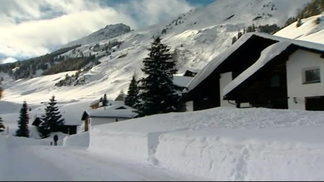 david cameron urges eu leaders to make bigger cuts ext snow covered chalets tilt down path workers clearing snow with shovels snow falling from tree... - jahreshauptversammlung stock-videos und b-roll-filmmaterial