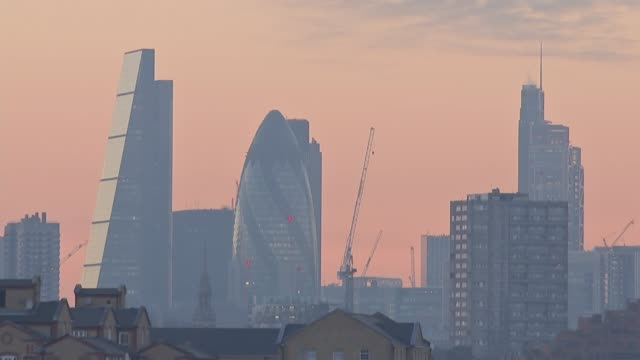 World Economic Forum in Davos / Global stock markets fall over price of oil ENGLAND London EXT City buildings at sunset including Gherkin and...
