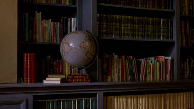 a world globe sits in front of bookshelves in a school library. - bookshelf stock videos & royalty-free footage