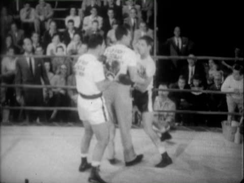 world heavyweight boxing champion rocky marciano wearing polkadot robe while climbing into boxing ring for muscular dystrophy fundraiser at... - 30代の男性点の映像素材/bロール