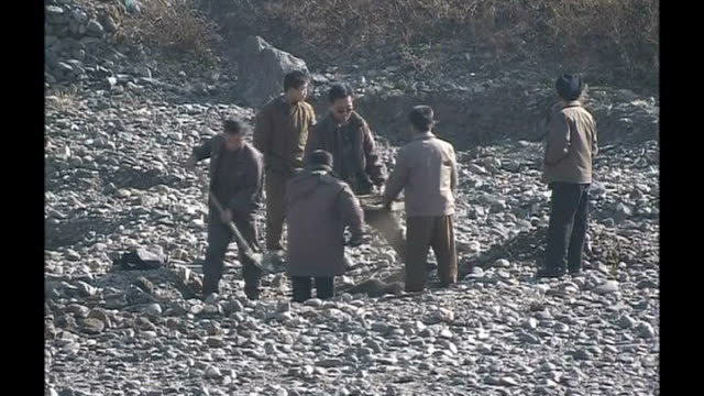 World leaders condemn rocket launch NORTH Poor people shovelling rocks in quarry as sifting for precious metals Man along with plastic container...