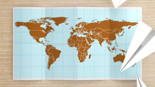 vídeos y material grabado en eventos de stock de mapa mundial se despliega y se convierte en el escritorio.  tres en uno. - avión de papel