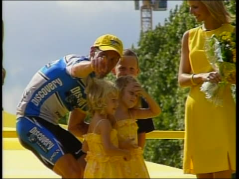 vidéos et rushes de world renown cyclist, lance armstrong stands on the winner's podium with the family after winning the tour de france. sheryl crow is also showed in... - sport