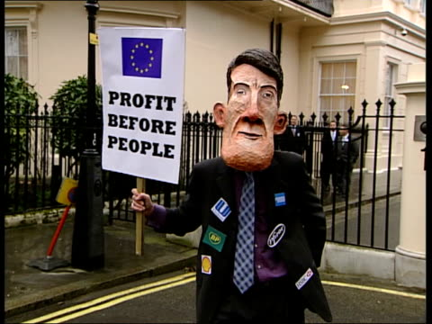 world trade organisation london protests; protestor wearing papier mache peter mandelson head holding 'profit before people' sign/ more of protestors... - papier stock videos & royalty-free footage