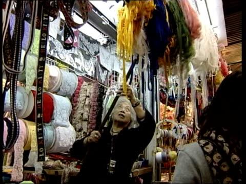 stockvideo's en b-roll-footage met world trade organisation talks preview: farming subsidies; china: hong kong: jardine's bazaar: ext lms denim clothes displayed on clothes market... - agrarisch beroep