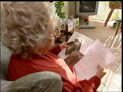 soldier shot for cowardice: pardon attempt; england: int gertrude harris sitting at home looking at photographs of her father cms copy of army letter... - segnale informativo video stock e b–roll