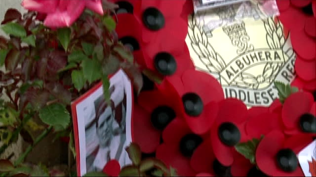 world war i centenary relatives of clapton orient volunteers visit france women laying wreath at grave photograph of george scott and poppy wreath... - リース点の映像素材/bロール