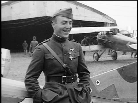 world war i flying ace leaning on airplane smiling after receiving croix de guerre - エディ リッケンバッカー点の映像素材/bロール