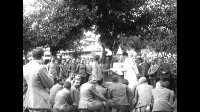ws world war i italian soldiers listen as priest conducts open air mass under a spreading tree at the carso front / ms priest stands in front of an... - prima guerra mondiale video stock e b–roll