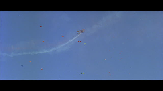 stockvideo's en b-roll-footage met ws pov  world war i jenny biplane airplane trailing colored smoke in air during air show - breedbeeldformaat