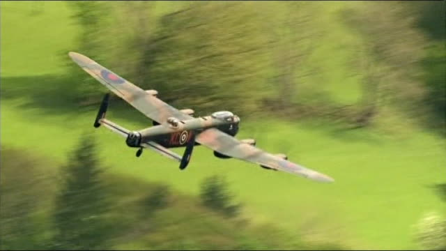 vídeos de stock e filmes b-roll de 70th anniversary of dambusters raid marked by flypast ext lancaster bomber flying over fields - avião bombardeiro
