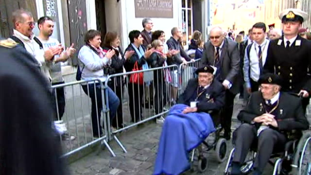 world war ii: 70th anniversary of d-day landings; british d-day veterans in wheelchairs along through centre of bayeux and cheered and applauded by... - itv news at ten点の映像素材/bロール