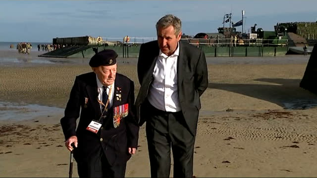 world war ii: 70th anniversary of d-day landings; france: normandy: ext peter thompson and reporter looking at small wooden crosses decrated with... - itv news at ten点の映像素材/bロール