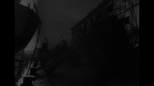 world war ii / aftermath of bombing of naples / wreckage of dock and many destroyed ships in naples bay / group of american soldiers surrounding an... - bombardamento video stock e b–roll
