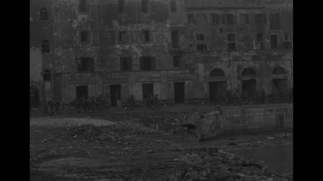 vídeos de stock, filmes e b-roll de world war ii / american soldiers clearing beach in anzio of debris / bombed-out buildings / soldiers marching along beachfront / ships at sea /... - world war ii