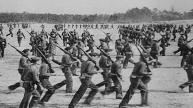world war ii basic military training including marching parade formation war games rifle instruction target practice and tanks driving past - military recruit点の映像素材/bロール
