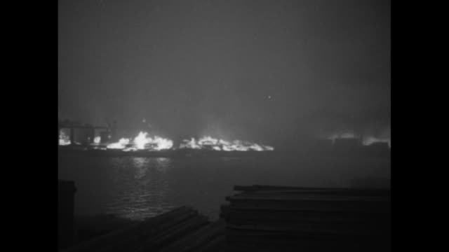world war ii / blitzkrieg / firefighter carries injured man at night / fires and smoke / buildings on fire at dock / firefighters with hose / water... - burning stock videos & royalty-free footage