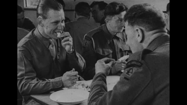 world war ii / british and american soldiers walking to barracks with all their gear / 2 soldiers claiming bunks / soldiers eating together in mess... - army soldier stock videos & royalty-free footage