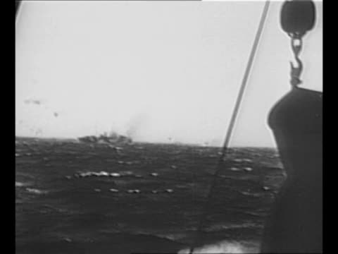 world war ii explosion near ship as seen from other ship in convoy / montage ships in convoy / waves and sea spray wash over prow of ship / black /... - 船の一部点の映像素材/bロール
