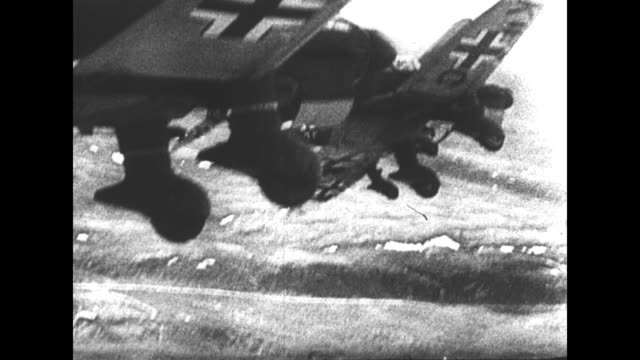 world war ii / german soldiers load bomb labeled murmansk onto plane / french language / german military airplanes in flight / bombs fall and explode... - french language stock videos & royalty-free footage