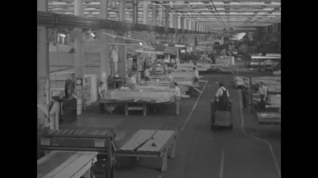 World War II / Home Front / interior aluminum factory / men working with sheets of aluminum / aluminum sheets on a press / sheets packed and stacked...