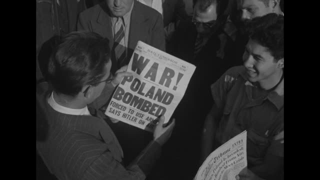 vídeos de stock e filmes b-roll de world war ii / homefront / men looking up at times square moving sign / man reading newspaper about germany invading poland / other headlines all... - 1939