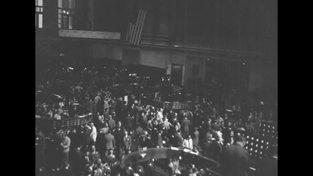 World War II / Homefront / statue of George Washington facing New York Stock Exchange / street scenes of NYSE / overhead busy trading floor of NYSE...