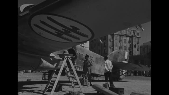 vidéos et rushes de world war ii / italian bomber in alexandria / insignias on plane / crowd of egyptian males watching / boys and men / raf airmen going over plane/ man... - alexandrie