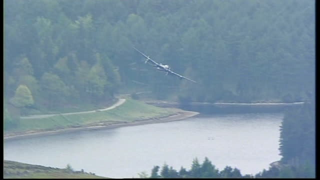 lancaster bomber flies over reservoir on dambusters' anniversary; england: derbyshire: derwent reservoir: ext * * theme music from 'the dam busters'... - bomber stock videos & royalty-free footage