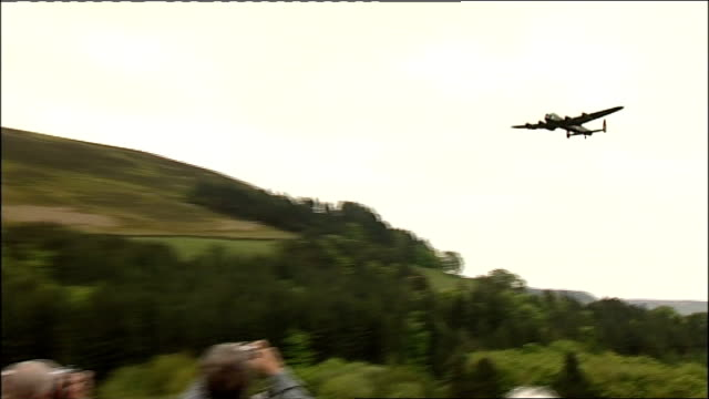 lancaster bomber flies over reservoir on dambusters' anniversary lancaster bomber plane flying over reservoir watched by crowd - lancaster bomber stock videos & royalty-free footage