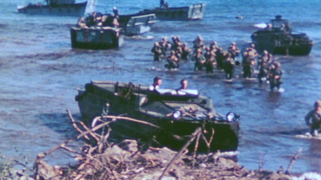 world war ii landing with marines wading in the shallows and lvts rolling into shore - water's edge stock videos & royalty-free footage