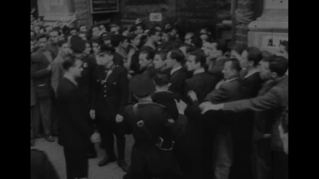 world war ii / large crowd italian people, mostly men, being herded and pushed around by italian police officers / sign amgot - allen military... - italian culture stock videos & royalty-free footage