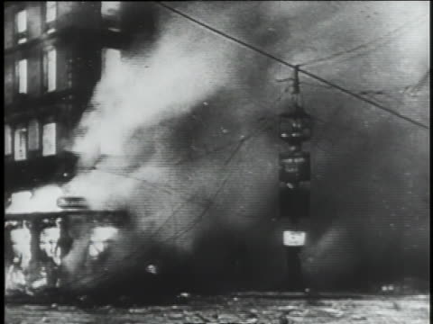 vidéos et rushes de world war ii military planes fly past a barrage balloon; bombed buildings collapse in flames; evacuees leave in trucks and cars; parisian mothers tearfully say goodby to their children who are being evacuated. - terrorisme