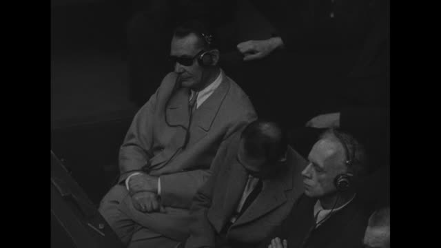 world war ii / nuremberg trial / ws courtroom people wearing headphones / defendants sit in the dock with mps surrounding them / defendants and court... - processi di norimberga video stock e b–roll
