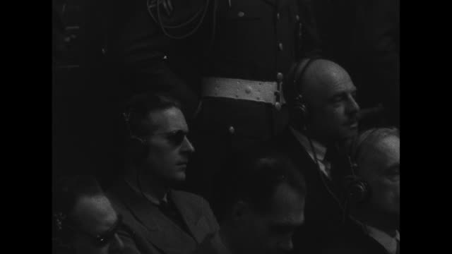 world war ii / nuremberg trial / defendants sit in the dock / most wearing headphones listening to proceedings / mps stand behind them - war crimes trial stock videos and b-roll footage