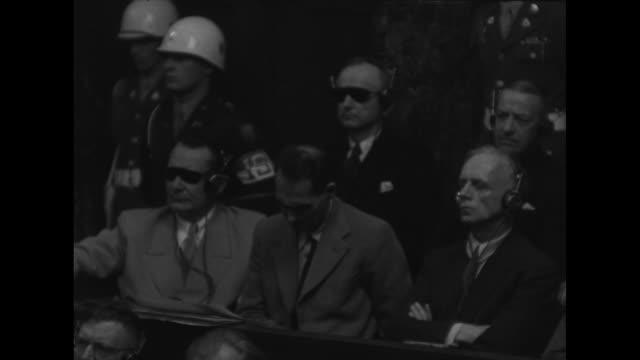 world war ii / nuremberg trial / defendants sit in the dock with mps surrounding them / hermann goering wears sunglasses / most wear headphones... - processi di norimberga video stock e b–roll