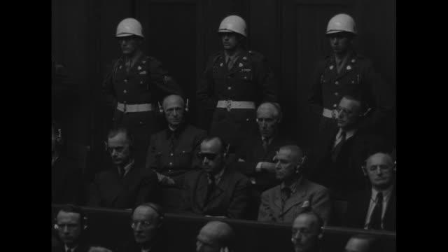 world war ii / nuremberg trial / defendants sit in the dock with mps surrounding them / hermann goering wears sunglasses / most wear headphones... - hermann goering stock videos & royalty-free footage