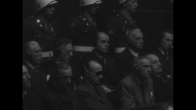 world war ii / nuremberg trial / ws defendants sit in the dock with mps surrounding them / vo foreign language / vo reading of verdict against albert... - nuremberg trials stock videos & royalty-free footage