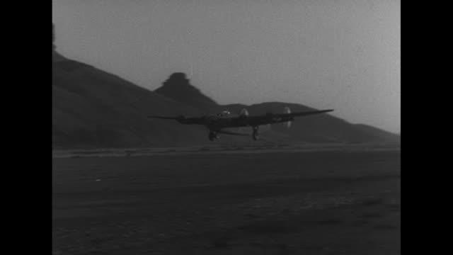 World War II / Pacific theater / interior plane with Gen Caleb Haynes and Maj D E Bailey at controls talking / B25 plane landing / ground crews...