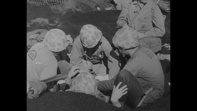 world war ii / pacific theater / iwo jima / corpsmen treating wounded us marine / japanese pows guarded and sitting in lci / pows board ship / cu... - battle of iwo jima stock videos and b-roll footage